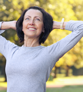 Smiling mature women stretching in park